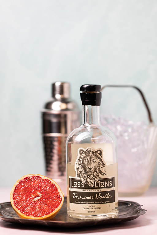 Half of a grapefruit and a bottle of Lass & Lions Vodka.