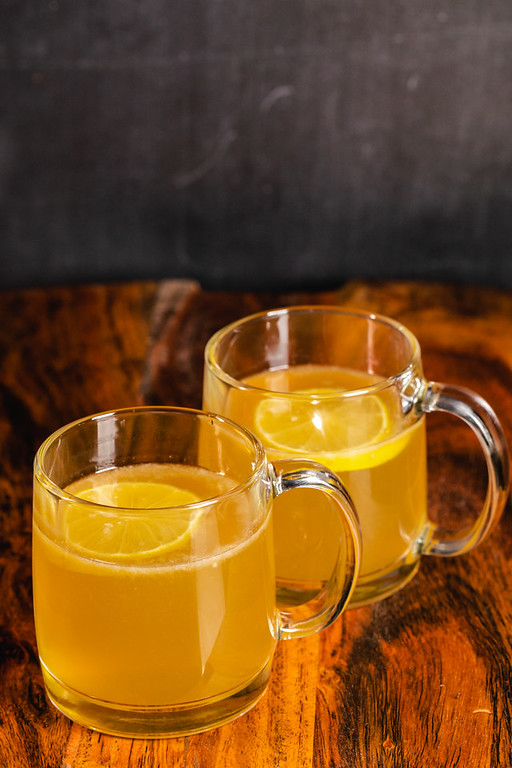 Two mugs filled with a hot toddy with a lemon floating on top.