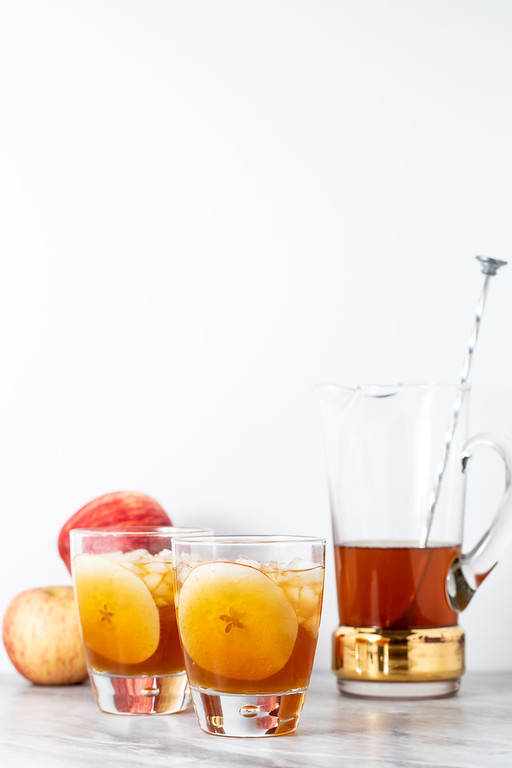 Two cocktails with apple slice garnish and a pitcher.