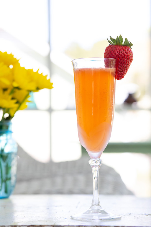 Strawberry ginger bellini in a glass garnished with a strawberry.