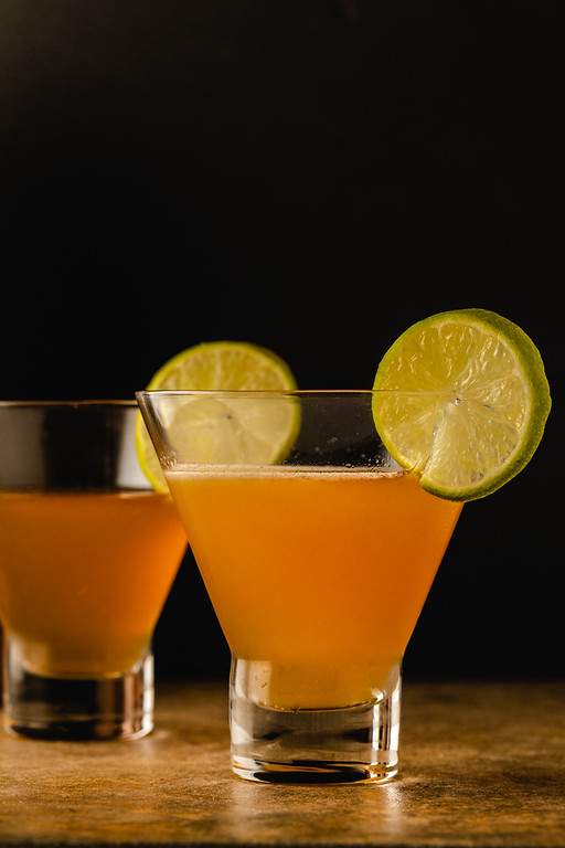 Two orange cocktails garnished with a lime wheel.