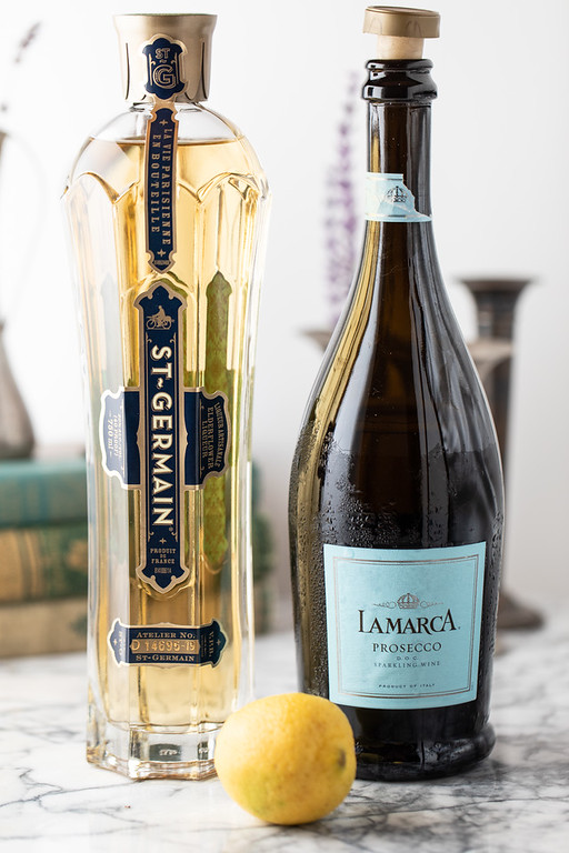 Ingredients to make a French 77, bottle of St. Germain, bottle of prosecco and a lemon.