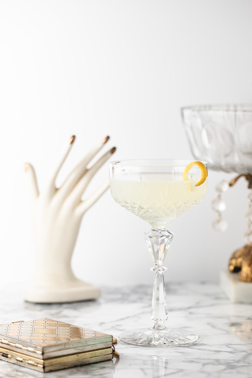 Coupe glass with white lady cocktail and gold and cream props.