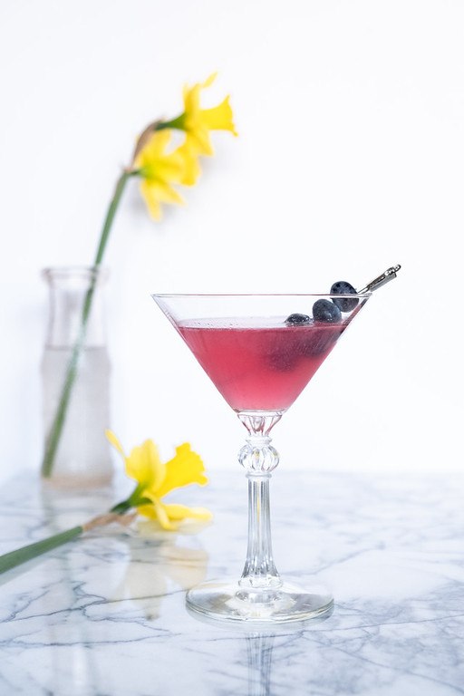 Blueberry elderflower martini in a glass garnished with blueberries.