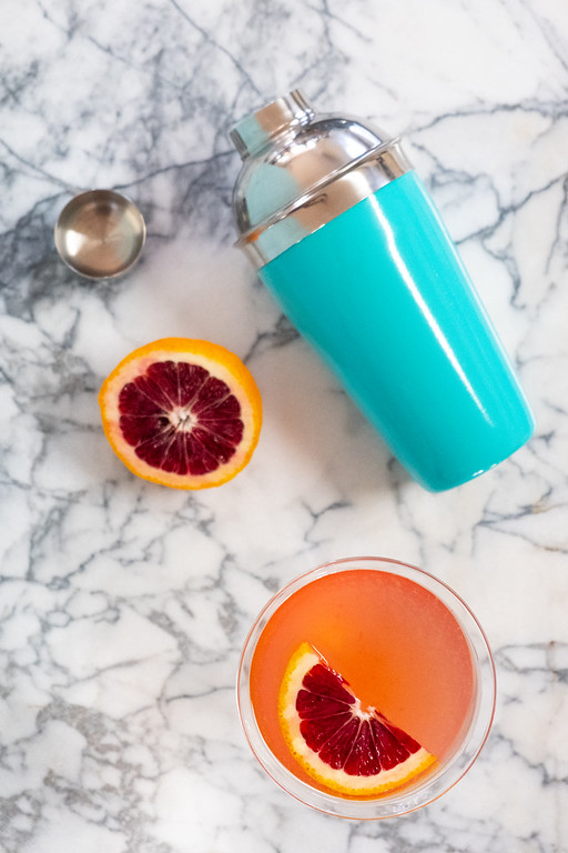 Blue cocktail shaker, overhead view of blood orange martini, on a marble tabletop.