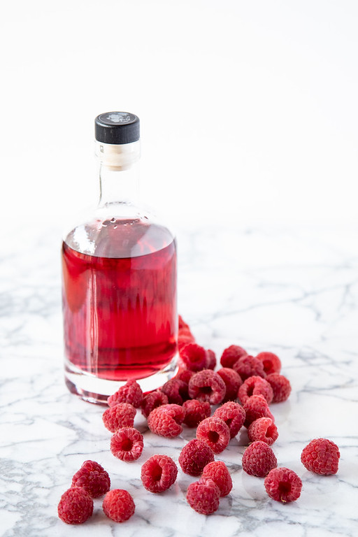Bottle of bright red liquid with raspberries scattered around.