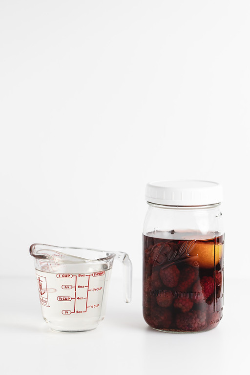Jar with blackberries and liquor and a cup of simple syrup.