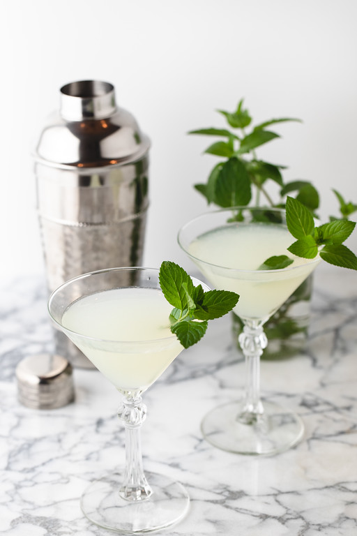Two martini glasses filled with a southside cocktail and garnished with mint.