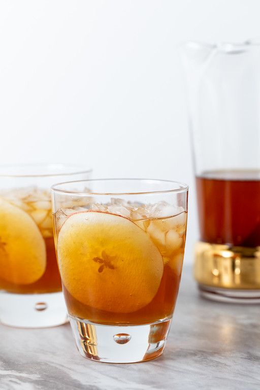 Two glasses with a dark and stormy cocktail garnished with apple slices.