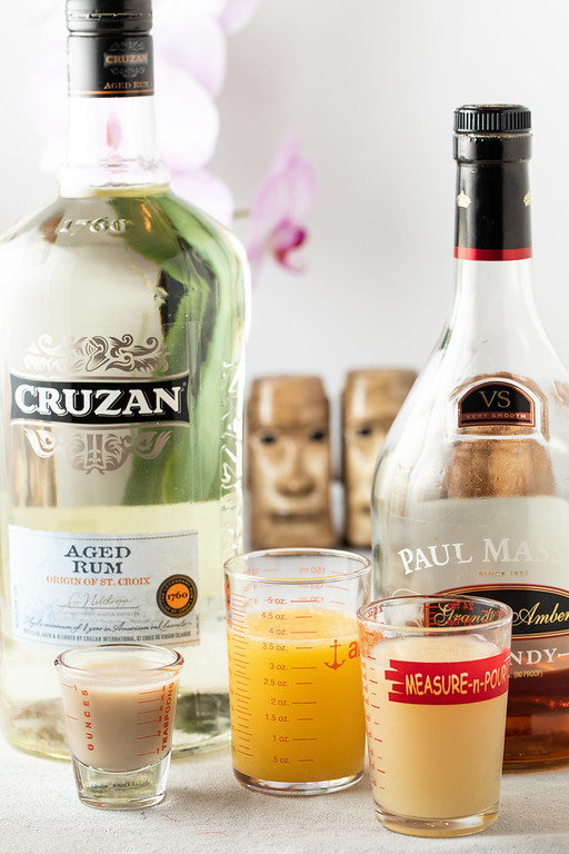Photo showing the ingredients in a scorpion cocktail, rum, orgeat syrup, orange juice, lemon juice, and brandy.