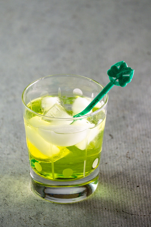 Light green cocktail with a green cocktail stirrer.