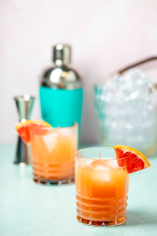 Two glasses filled with a bright orange cocktail garnished with a pink grapefruit wedge.