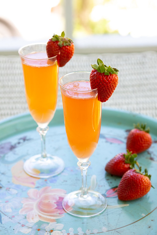 Two glasses of Strawberry Ginger Bellini on a blue tray.