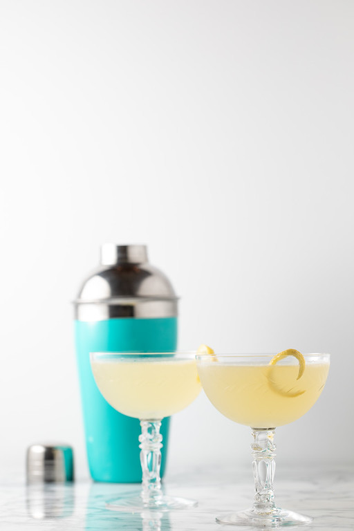 Two coupe glasses with bees knees cocktail.
