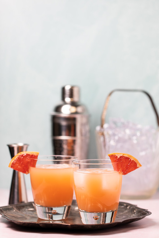 Two glasses filled with an orange cocktail and garnished with grapefruit wedges.