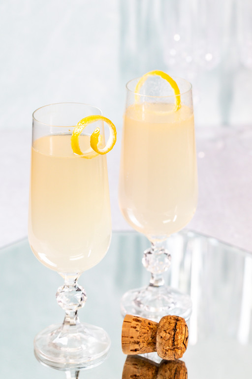 Two glasses filled with a light yellow cocktail and a champagne cork in front of them.