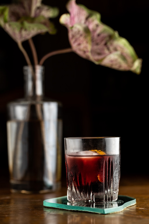 Glass filled with dark cherry colored liquid, an ice cube and garnished with an orange peel.
