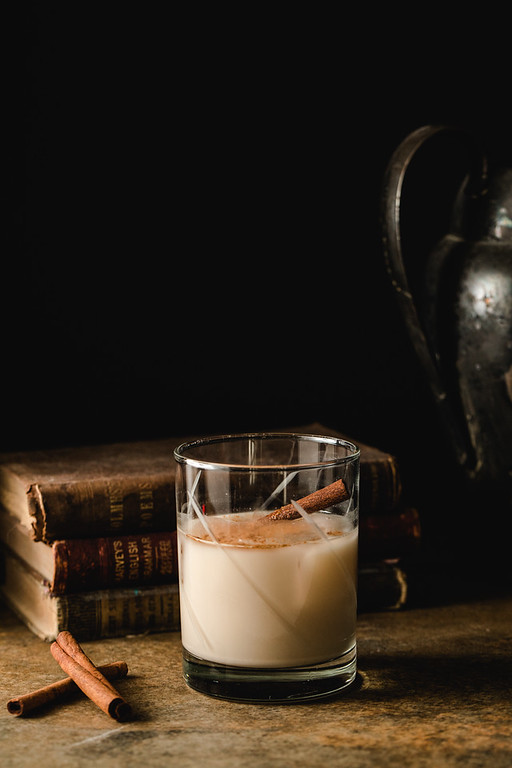Glass with homemade rumchata and cinnamon stick in front of books.