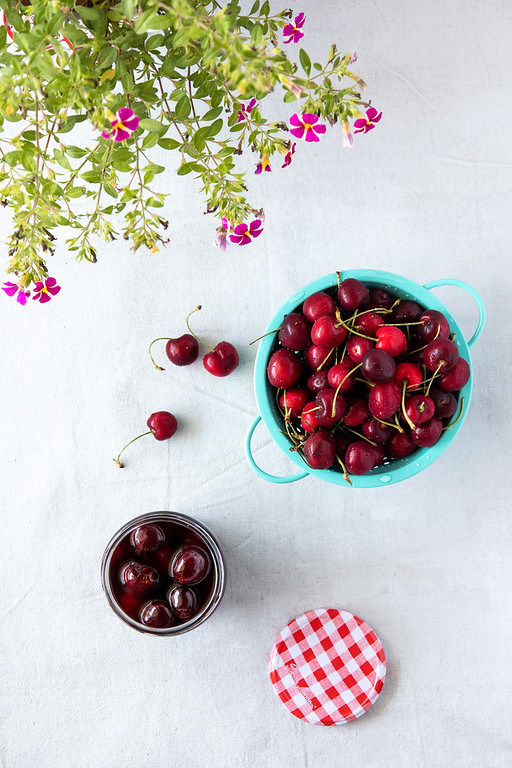Top down view of maraschino cherries in a jar, with a bowl of cherries.