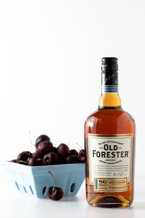 Bottle of Old Forester Bourbon and a container of cherries.