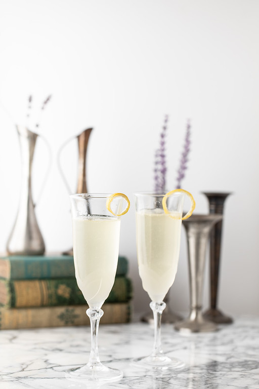 Two glasses of French 77 garnished with a lemon twist.