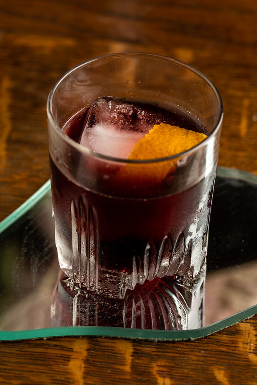 Glass filled with a dark red cocktail, large ice cube and orange twist.