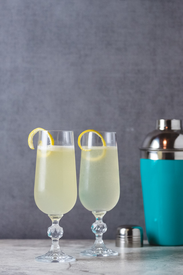 Two cocktail flutes filled with a light yellow liquid, garnished with lemon twists in front of a gray wall with a blue cocktail shaker