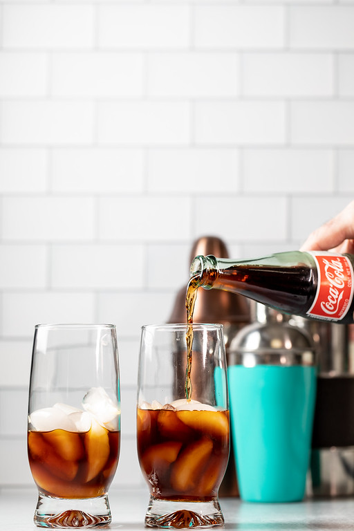Adding Coke to Fernet-Branca in a glass.