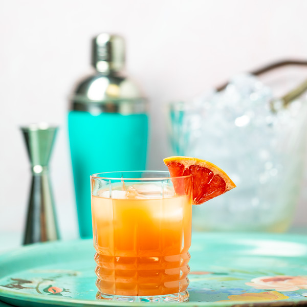 Cocktail glass filled with a dark orange cocktail garnished with a grapefruit wedge.