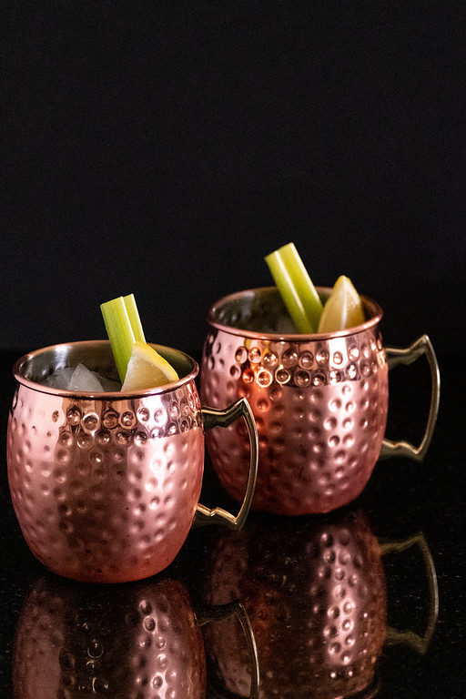 Two copper moscow mule mugs with celery stick and lemon wedge.