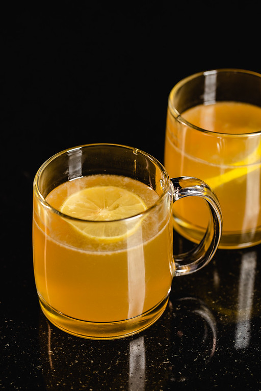 Two mugs of a dark orange liquid with a lemon slice floating on top.