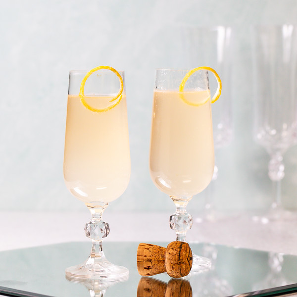 Two cocktail glasses filled with a light yellow cocktail and popped champagne cork in front.