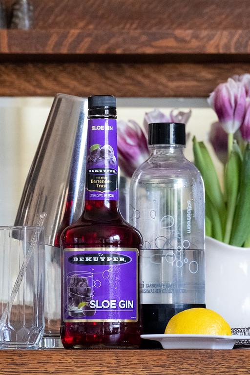 Bottle of sloe gin, glass, lemon half and sparkling water.