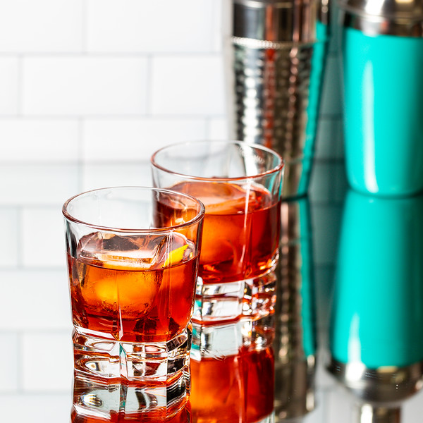 Two cocktail glasses filled with a deep reddish brown cocktail.