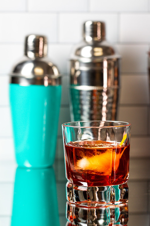 Cocktail glass with a deep reddish brown cocktail and cocktail shakers behind it.