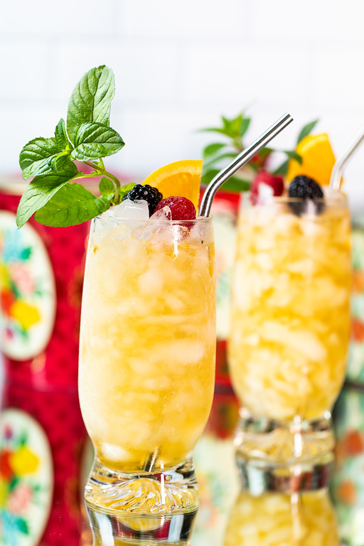 Two bright yellow cocktails garnished with mint, raspberries, blackberries, orange slice and a metal straw.