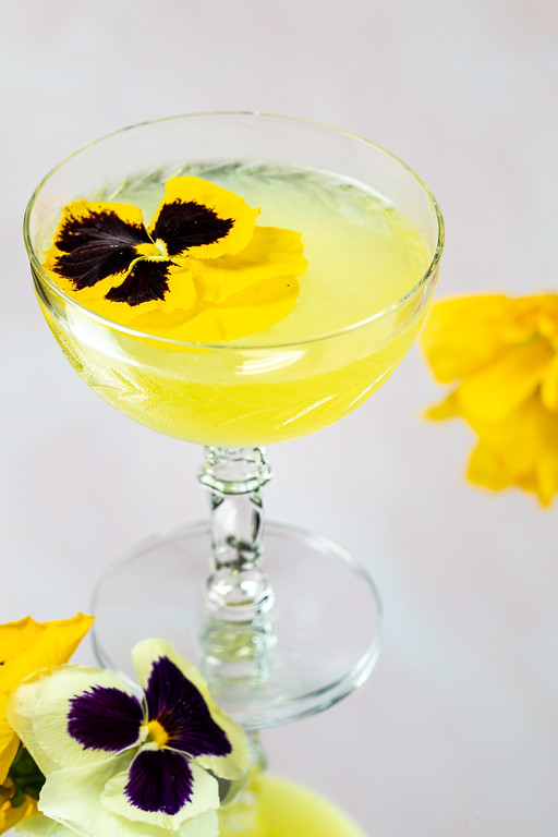 Bright yellow cocktail with a pansy flower garnish.