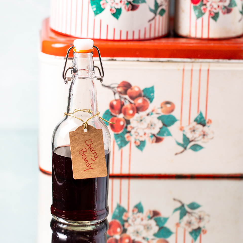 Bottle of homemade cherry brandy in front of a vintage tin.