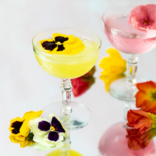 Bright yellow cocktail garnished with a pansy flower!