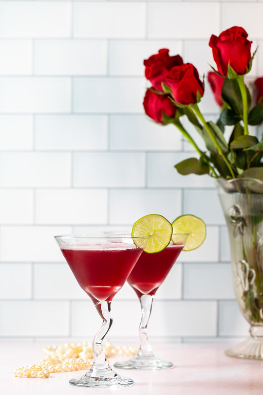 Two martini glasses filled with a deep pink cocktail.