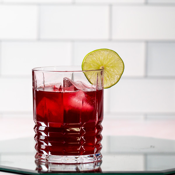 Deep red cocktail garnished with a lime wheel.