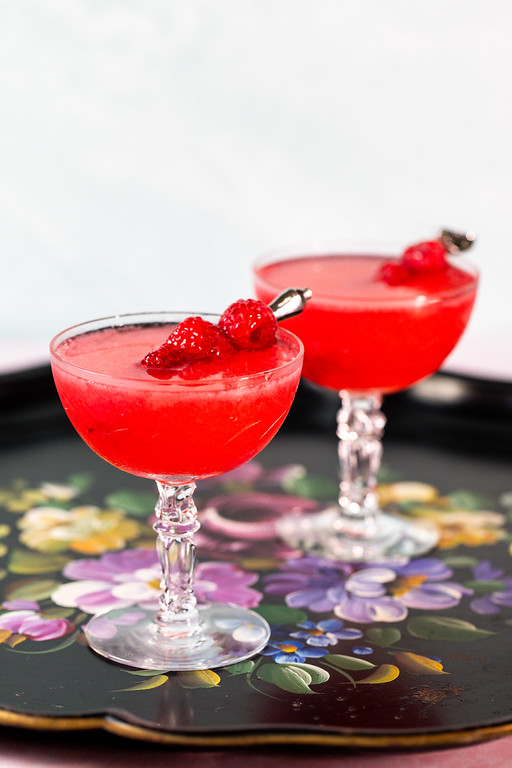 Two deep red cocktails on a black floral tole tray.