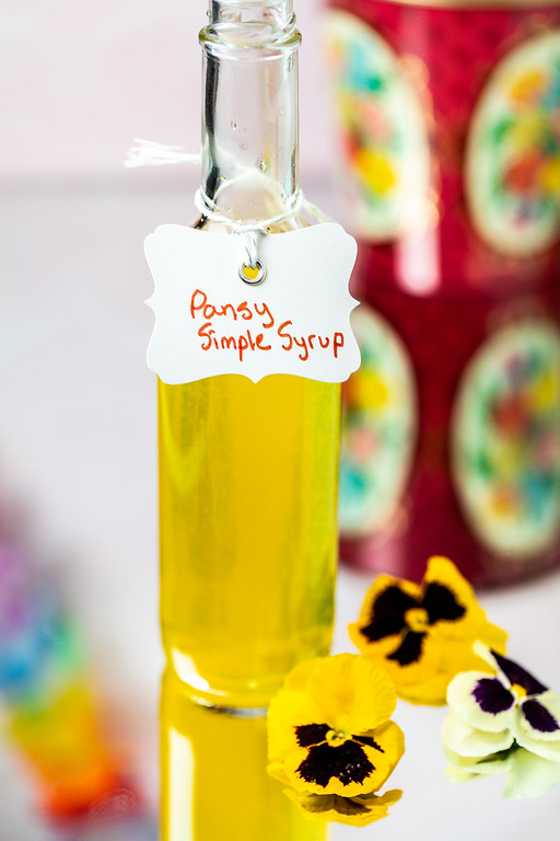 Bottle filled with bright yellow liquid with tag reading pansy simple syrup.