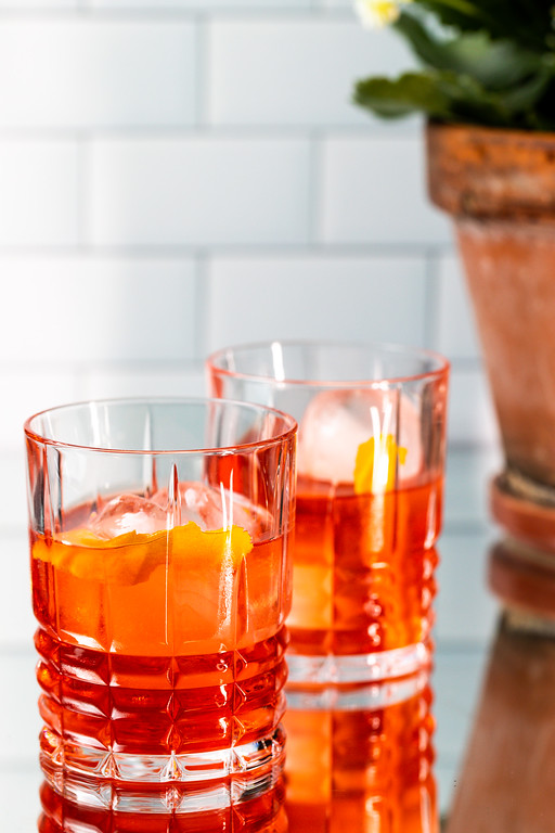 Two cocktail glasses filled with a vibrant red orange cocktail.