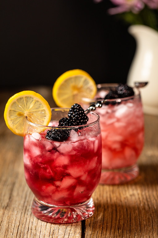 Dark pink cocktail garnished with blackberries and a lemon wheel.
