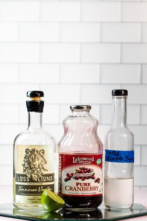 Vodka, cranberry juice, lemon half and simple syrup to make a vodka cranberry.