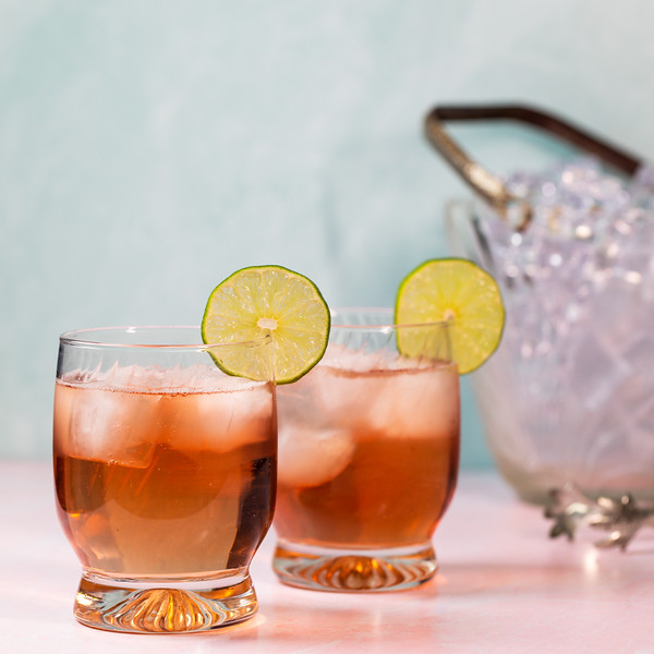 Two glasses filled with a pink cocktail garnished with a lime wheel.