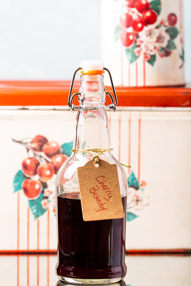 Bottle of deep red liquor with a tag reading Cherry Brandy.