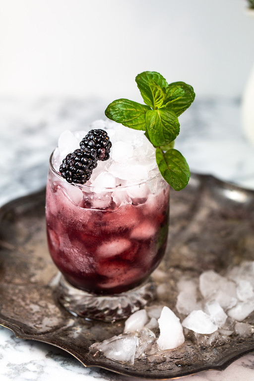 Dark purple cocktail in a glass filled with crushed ice and garnished with blackberries and mint.