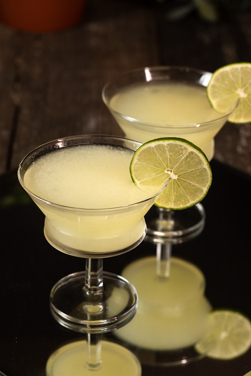 Two yellow cocktails garnished with a lime peel.